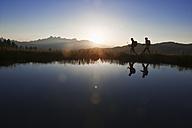 Austria, Salzburg, Couple walking near mountain lake at sunrise - HHF003776