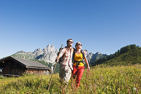 Austria, Salzburg, Filzmoos, Couple walking through meadow - HHF003822