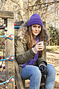 Germany, Berlin, Wandlitz, Mid adult woman drinking coffee at playground, portrait - WESTF018315