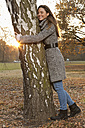Germany, Berlin, Wandlitz, Mid adult woman hugging tree, smiling - WESTF018339