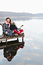 Germany, Berlin, Wandlitz, Couple sitting on pier, smiling - WESTF018348
