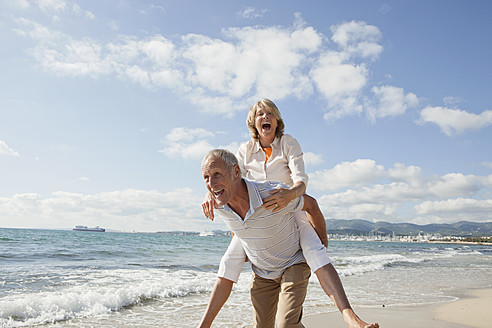 Spain, Mallorca, Senior man giving piggy back ride to woman at beach - SKF000846