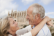 Spain, Mallorca, Palma, Senior couple smiling with Cathedral Santa Maria, portrait - SKF000864