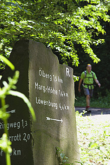 Europe, Germany, North Rhine Westphalia, Hiking trail sign with hiker in background - GWF001670