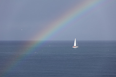 Ireland, Leinster, County Fingal, View of boat in sea with rainbow - SIEF002204