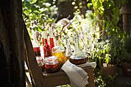 Austria, Salzburg, Flachau, Variety of herbal oils on chair - HHF003891
