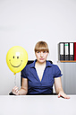 Germany, Businesswoman holding smiley face balloon - ANBF000074