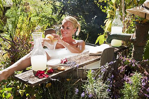 Austria, Salzburg, Flachau, Young woman taking milkbath in tun - HHF003922