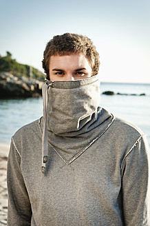 Spain, Mallorca, Young man in sweatshirt on beach, portrait - MFPF000001