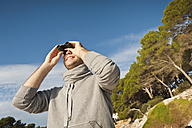 Spain, Mallorca, Young man looking through binocular, smiling - MFPF000019