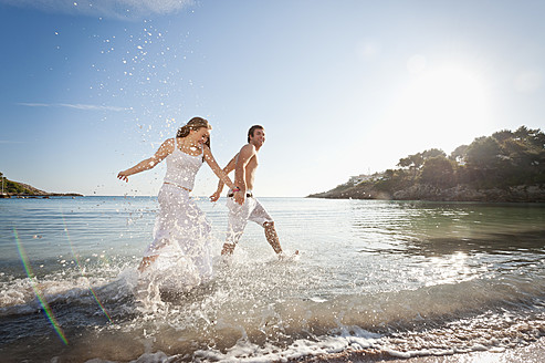 Spain, Mallorca, Couple running along beach - MFPF000025