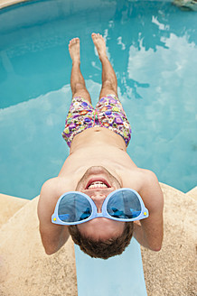 Spain, Mallorca, Young man with funny glasses on diving board, smiling - MFPF000037