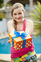 Spain, Mallorca, Teenage girl holding gift box, smiling, portrait - MFPF000043