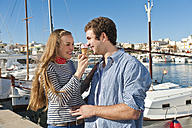 Spain, Mallorca, Couple eating ice cream at harbour, smiling - MFPF000058