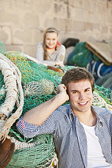 Spain, Mallorca, Couple at harbour with fishing nets, smiling, portrait - MFPF000064