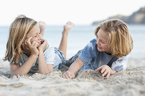 Spain, Mallorca, Children lying in sand on beach, smiling - MFPF000097