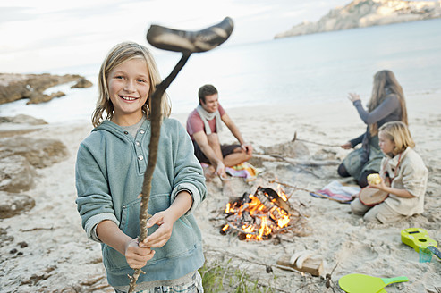 Spain, Mallorca, Friends with sausages at camp fire on beach - MFPF000109