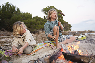 Spain, Mallorca, Children barbecueing sausages on beach - MFPF000118
