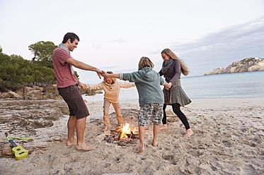 Spain, Mallorca, Friends dancing at camp fire on beach - MFPF000121