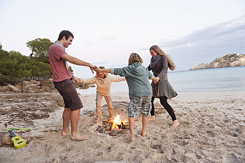 Spain, Mallorca, Friends dancing at camp fire on beach - MFPF000121