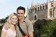 Spain, Mallorca, Palma, Couple standing with St Maria Cathedral in background, smiling, portrait - SKF000876