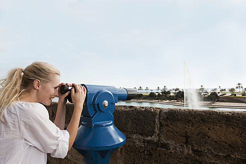 Spain, Mallorca, Palma, Young woman looking through telescope, smiling - SKF000927