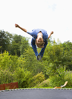 Austria, Young man jumping on trampoline - WWF002093