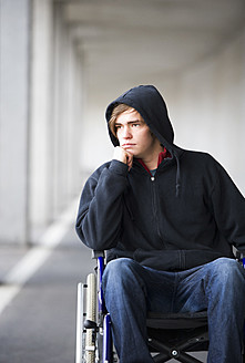 Austria, Mondsee, Young man sitting on wheelchair at subway - WWF002101