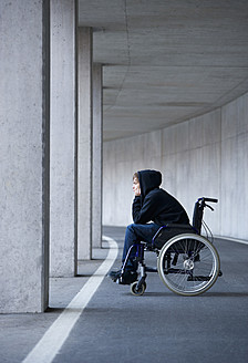Austria, Mondsee, Young man sitting on wheelchair at subway - WWF002102