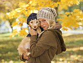Austria, Young woman holding dog in autumn, portrait, close up - WWF002152