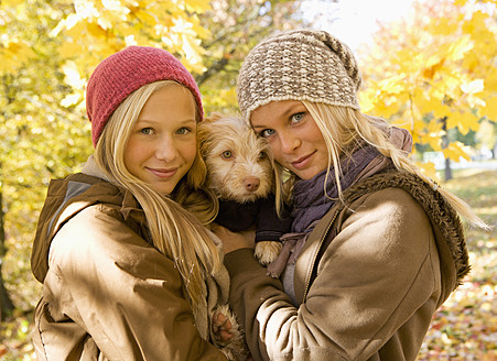 Austria, Sisters holding dog in autumn, smiling, portrait - WWF002330
