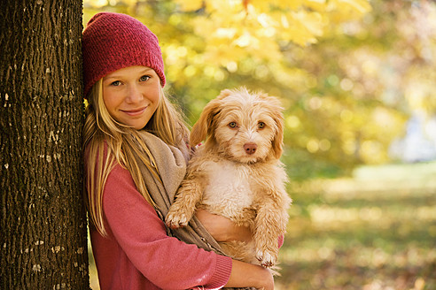 Austria, Teenage girl holding dog besides tree, smiling, portrait - WWF002161
