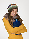 Teenage girl with hot water bottle, smiling, portrait - WWF002302