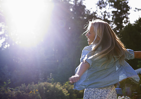 Austria, Teenage girl dancing in sunlight - WWF002262