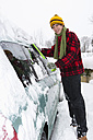 Austria, Young man cleaning snow on car - WWF002124