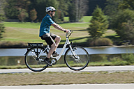Germany, Bavaria, Mature man riding electric bicycle - DSF000241