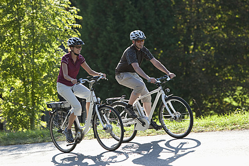 Germany, Bavaria, Man and woman riding electric bicycle - DSF000244