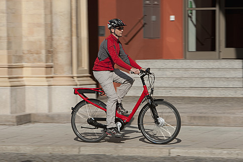Germany, Bavaria, Munich, Mature man riding electric bicycle - DSF000247