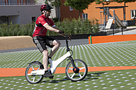 Germany, Bavaria, Munich, Mature man riding electric bicycle - DSF000253