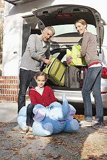 Germany, Leipzig, Family loading luggage into car, smiling, portrait - WESTF018430