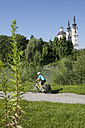 Austria, Carinthia, Villach, Mid adult woman riding bicycle - DSF000265