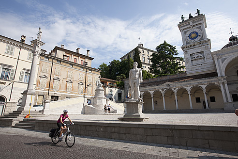 Italy, Udine, Mid adult woman riding bicycle - DSF000268