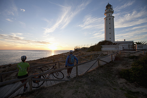 Spain, Andalusia, Man and woman standing by light house, watching sunset - DSF000289