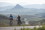 Spain, Andalusia, Vejer, Man and woman cycling through country road - DSF000296