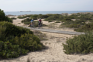 Spain, Andalusia, Man and woman cycling on boardwalk - DSF000273