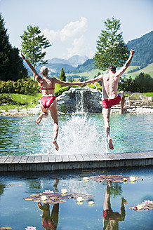 Austria, Salzburg County, Couple jumping into swimming pool - HHF003962