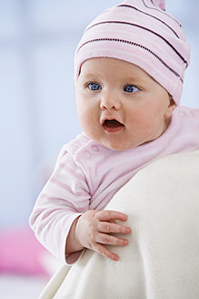 Baby girl in woolly hat with mouth open, close up - SMOF000512