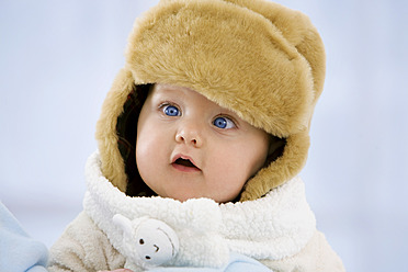 Baby girl in fur hat with mouth open, close up - SMOF000517