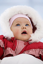 Baby girl in snow suit with mouth open - SMOF000521