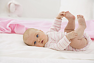 Baby girl lying on baby blanket with holding foot - SMOF000522